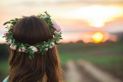 Flicka i en krans som tycker om solnedgången i ängen royaltyfria foton