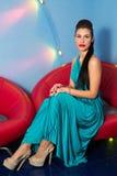 Flicka i en lång klänning och höga häl i studion arkivbild
