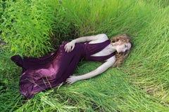 Flicka i en lång lilaklänning Fotografering för Bildbyråer