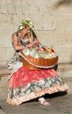 Flicka i en ljus klänning som rymmer en korg av blommor Royaltyfri Bild
