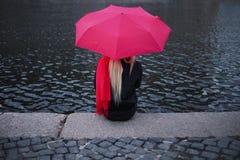 Flicka i en ljus rosa halsduk, gummistöveler och paraplysammanträde på bankerna av floden, baksida Grått grymt landskap royaltyfri foto