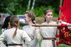 Flicka i en medeltida dräkt som rymmer ett baner Arkivbild