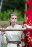 Flicka i en medeltida dräkt som rymmer ett baner Royaltyfri Foto
