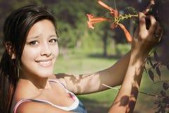 Flicka i en parkera med blomman Arkivfoto