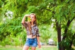 Flicka i en plädskjorta och jeans som rymmer en grupp av grön druvanärbild Begrepp av att skörda en koloni av druvor och en flick arkivbild