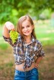 Flicka i en plädskjorta och jeans som rymmer en grupp av grön druvanärbild Begrepp av att skörda en koloni av druvor och en flick royaltyfria foton