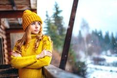 Flicka i en rät maskatröja som ser snö Arkivbild