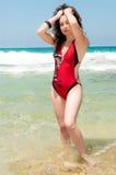 Flicka i en röd baddräkt med hennes hår Arkivbild