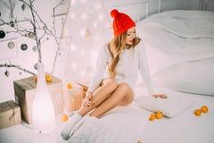 Flicka i en röd hatt som går i nattgatan royaltyfri foto