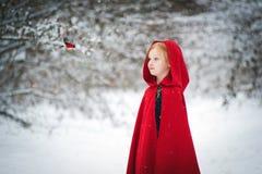 Flicka i en röd regnrock med en fågel arkivbild