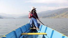 Flicka i en röd skjorta, hatt och solglasögon i ett träblått fartyg med en skovel i hennes händer, på sjön mot bakgrunden av gr stock video