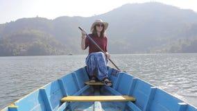 Flicka i en röd skjorta, hatt och solglasögon i ett träblått fartyg med en skovel i hennes handleenden och samtal, på sjön mot arkivfilmer