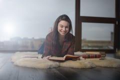 Flicka i en röd skjorta som ligger på mattan Arkivfoto