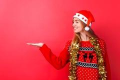 Flicka i en röd tröja och jultomtenhatt, med glitter runt om hennes hals som pekar på ett tomt utrymme på en röd bakgrund royaltyfria foton