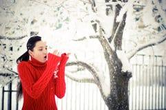 Flicka i en röd tröja och snow Royaltyfria Foton