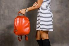Flicka i en randig klänning som rymmer den röda påsen arkivfoton