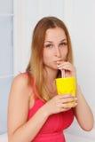 Flicka i en rosa klänning med den gula glass handen arkivbild