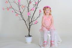 Flicka i en rosa krans och en rosa klänning med en fågel på en flowerin Royaltyfria Bilder