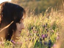 Flicka i en sätta in av blommor arkivbilder