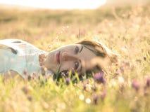 Flicka i en sätta in av blommor arkivfoton