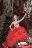 Flicka i en smart röd klänning Fotografering för Bildbyråer