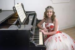 Flicka i en smart vit klänning med röda blommor arkivfoto
