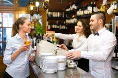 Flicka i en stång med exponeringsglas av vin Royaltyfri Fotografi