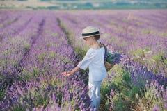 Flicka i en sugrörhatt i ett fält av lavendel med en korg av lavendel En flicka i ett lavendelfält Flicka med en bukett av lavend Arkivfoto