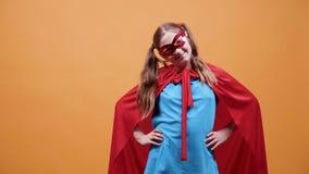 Flicka i en superherodräkt som ler till kameran arkivfilmer