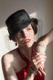Flicka i en svart hatt med en skyla Arkivfoto