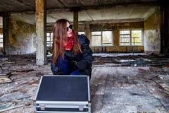 Flicka i en svart kappa med en diplomat i ett förstört rum En spion i ett hemligt möte Ovanlig fotofors arkivfoton