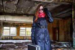 Flicka i en svart kappa med en diplomat i ett förstört rum En spion i ett hemligt möte Ovanlig fotofors arkivbild