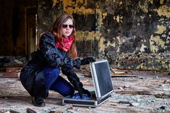 Flicka i en svart kappa med en diplomat i ett förstört rum En spion i ett hemligt möte Ovanlig fotofors arkivfoto