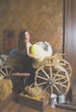 Flicka i en svart klänning med ett stort ägg i dina händer Arkivbild