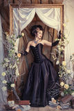 Flicka i en svart klänning på en ljus bakgrund Royaltyfria Bilder