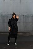 Flicka i en svart klänning som poserar i parkeringsplatsen Arkivbild