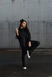 Flicka i en svart klänning som poserar i parkeringsplatsen Fotografering för Bildbyråer