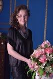 Flicka i en svart klänning bredvid en vas med blommor Arkivfoton