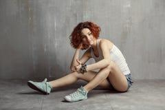 Flicka i en väst och gymnastikskor som sitter på en grå bakgrundstextur Royaltyfria Bilder