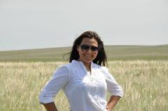 Flicka i en vit blus och solglasögon i sommarfält Royaltyfri Bild