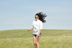 Flicka i en vit blus och solglasögon i sommarfält Arkivfoton