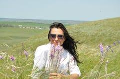Flicka i en vit blus och solglasögon i sommarfält Royaltyfria Bilder