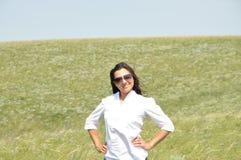 Flicka i en vit blus och solglasögon i sommarfält Royaltyfri Foto