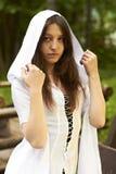 Flicka i en vit dräkt med en fantasihuv Arkivbild