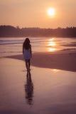 Flicka i en vit klänning på solnedgången Arkivbild