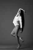 Flicka i en vit kropp som poserar i studion på en svart bakgrund Arkivbild