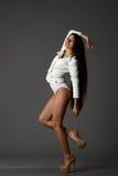 Flicka i en vit kropp som poserar i studion på en svart bakgrund Arkivbilder