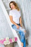 Flicka i en vit T-tröja och jeans Arkivfoton