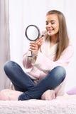 Flicka i ett badrocksammanträde på sängen Royaltyfri Foto
