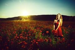 Flicka i ett blommandefält Modestående av en sinnlig sexig flicka opier, kvinna eller lycklig flicka i fält av vallmofrö Arkivfoto